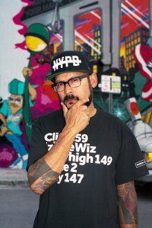 Alan Ket, co-founder of the Museum of Graffiti, in front of a detail of a mural created by Yes 2, Doves and Mast (2019)