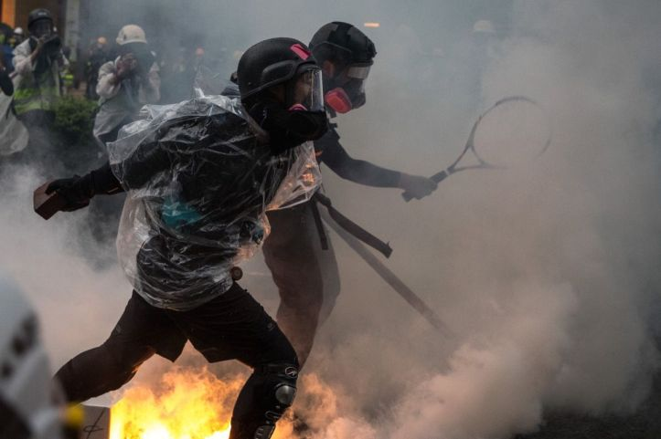 """HONG KONG - AUGUST 25: Protesters clash with police after an anti-government rally in Tsuen Wan district on August 25, 2019 in Hong Kong, China. Pro-democracy protesters have continued rallies on the streets of Hong Kong against a controversial extradition bill since 9 June as the city plunged into crisis after waves of demonstrations and several violent clashes. Hong Kong's Chief Executive Carrie Lam apologized for introducing the bill and declared it """"dead"""", however protesters have continued to draw large crowds with demands for Lam's resignation and complete withdrawal of the bill. (Photo by Chris McGrath/Getty Images)"""