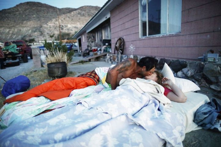TRONA, CALIFORNIA - JULY 08: Chimene Jackson kisses her husband Johnnie shortly after dawn outside her parents' home, which has been deemed uninhabitable due to structural damage from the recent 7.1 magnitude earthquake, on July 8, 2019 in Trona, California. Homeowners Benny and Anna Sue Eldridge, husband and wife, are currently sleeping outside the home with other family members on mattresses and in trucks for safety. Firefighters told them a stronger earthquake could cause the house to collapse. Anna Sue's father constructed the home with Benny's help in 1961. During the daytime they have been packing furniture, heirlooms and other items to place into storage as they try to decide where they will live next or if they will rebuild. (Photo by Mario Tama/Getty Images)