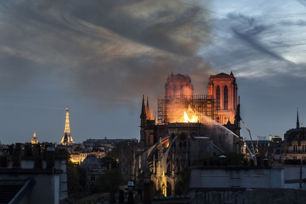 PARIS, FRANCE - APRIL 15: Flames and smoke are seen billowing from the roof at Notre-Dame Cathedral on April 15, 2019 in Paris, France. A fire broke out on Monday afternoon and quickly spread across the building, collapsing the spire. The cause is yet unknown but officials said it was possibly linked to ongoing renovation work. (Photo by Veronique de Viguerie/Getty Images)