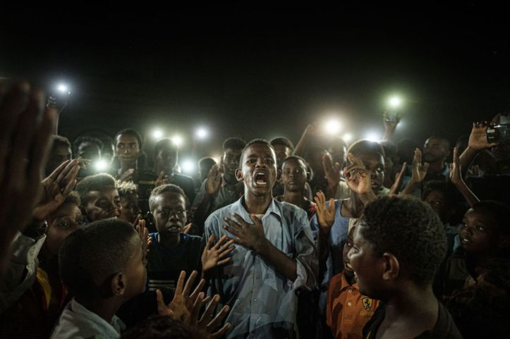 """TOPSHOT - People chant slogans as a young man recites a poem, illuminated by mobile phones, before the opposition's direct dialog with people in Khartoum on June 19, 2019. - People chanted slogans including """"revolution"""" and """"civil"""" as the young man recited a poem about revolution. (Photo by Yasuyoshi CHIBA / AFP) (Photo credit should read YASUYOSHI CHIBA/AFP/Getty Images)"""
