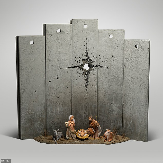 The 'Scar of Bethlehem' (pictured) features a nativity scene with Mary and Joseph and the baby Jesus - but instead of a star hanging over the crib, there is what appears to be a large bullet hole piercing an imposing grey wall