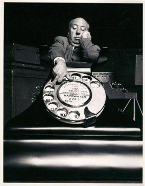 """Alfred Hitchcock con il gigantesco mock-up di un telefono che aveva costruito per i titoli di coda di """"Il delitto perfetto"""" (1954)"""