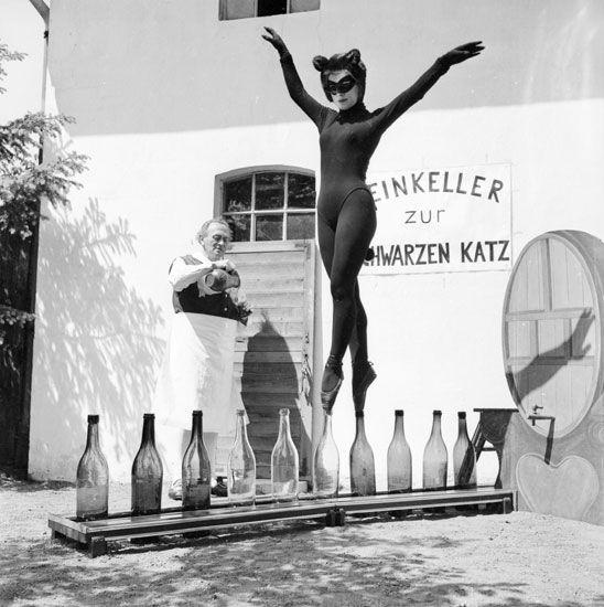 Bianca Passarge vestita in una tuta da ginnastica, cammina su bottiglie di vetro. 1940