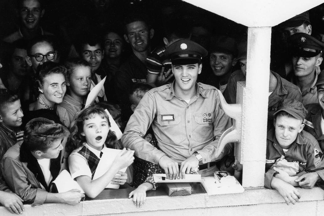 Elvis sorride e lancia baci ai fan mentre il Generale Randall si allontana dal molo nel 1958. Fotografia di Bill Ray