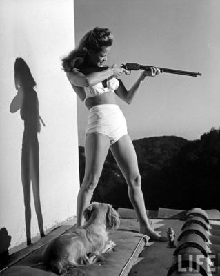L'attrice Dona Drake prende scherzosamente la mira con un fucile sul balcone della sua casa di Los Angeles, 1942