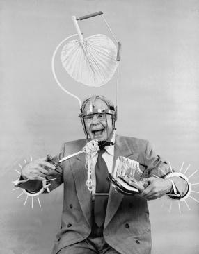Circa 1955: Russell E. Oakes, un inventore americano dilettante, indossa alcune delle sue invenzioni. Le punte sulle sue braccia gli permettono di farsi strada attraverso un grande magazzino pieno di gente. Ha anche inventato un mangiatore di spaghetti a carica e uno strano aggeggio a ventaglio per la testa