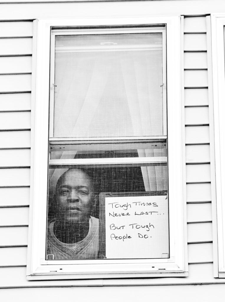 Robert E. Clark Jr. poses for 'Words At The Window: Self Isolation And The Coronavirus', a portrait series by Shutterstock Staff Photographer, Stephen Lovekin, shot around the Ditmas Park neighborhood of Brooklyn, New York.