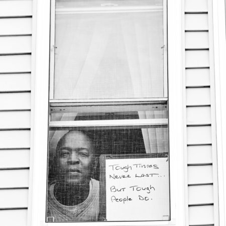 Robert E. Clark Jr. poses for 'Words At The Window: Self Isolation And The Coronavirus', a portrait series by Shutterstock Staff Photographer, Stephen Lovekin, shot around the Ditmas Park neighborhood of Brooklyn, New York.