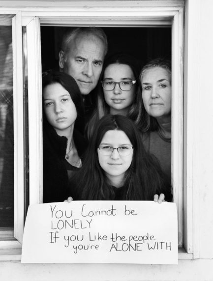 Tom Smith and Laura Ross, with daughters Caroline, Elizabeth, and Abigail, pose for 'Words At The Window: Self Isolation And The Coronavirus', a portrait series by Shutterstock Staff Photographer, Stephen Lovekin, shot around the Ditmas Park neighborhood of Brooklyn, New York.