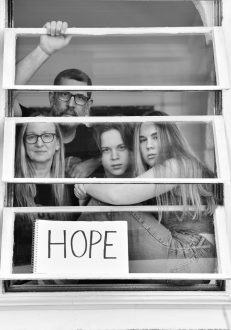 Agnetha Septimus, Matthew Septimus, and children Ezra and Nora, pose for 'Words At The Window: Self Isolation And The Coronavirus', a portrait series by Shutterstock Staff Photographer, Stephen Lovekin, shot around the Ditmas Park neighborhood of Brooklyn, New York.