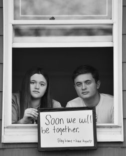 Callie Lovekin and Lucas Lovekin pose for 'Words At The Window: Self Isolation And The Coronavirus', a portrait series by Shutterstock Staff Photographer, Stephen Lovekin, shot around the Ditmas Park neighborhood of Brooklyn, New York.