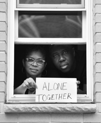Husband and wife filmmakers, Claire Ince and Ancil McKain pose for 'Words At The Window: Self Isolation And The Coronavirus', a portrait series by Shutterstock Staff Photographer, Stephen Lovekin, shot around the Ditmas Park neighborhood of Brooklyn, New York.