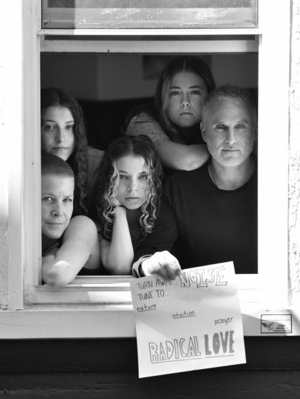 Jean Davis and Danny Rosenthal, with children Simone, Naomi, and Leah, pose for 'Words At The Window: Self Isolation And The Coronavirus', a portrait series by Shutterstock Staff Photographer, Stephen Lovekin, shot around the Ditmas Park neighborhood of Brooklyn, New York.