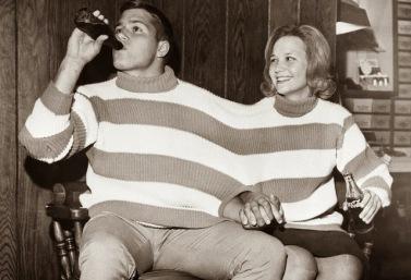 """17 ottobre 1963: Tommy Harper e Chica Grey condividono un maglione costruito per due in un negozio del centro. Il """"Tweter"""", come lo chiamavano, era destinato a essere la nuova tendenza della moda con due maniche, due dolcevita e un giromanica centrale."""