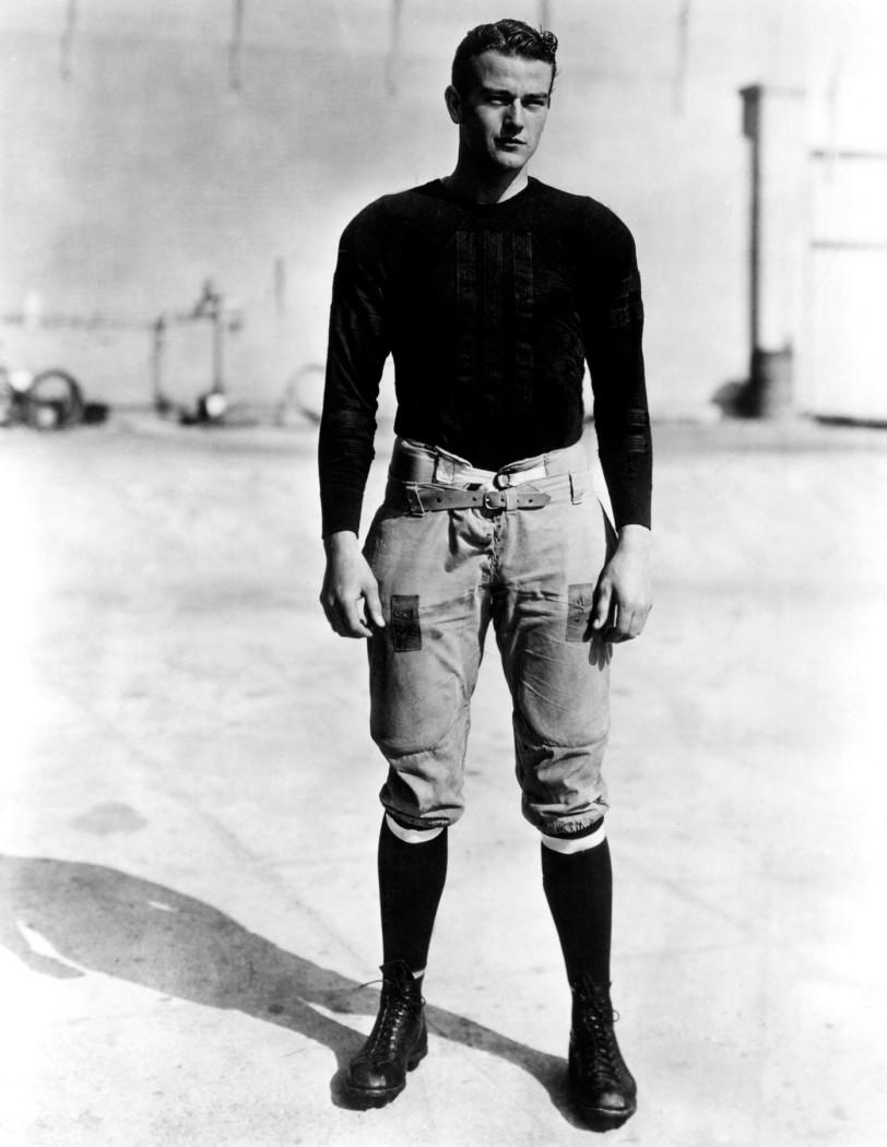 """Il diciannovenne John Wayne sul set del suo primo film. Ha interpretato un giocatore di football di Yale in """"The Brown of Harvard"""" nel 1926"""