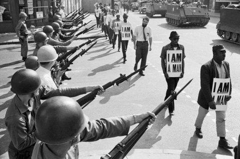 """Manifestanti afro-americani indossano cartelli con scritto """"Io sono un uomo"""" mentre marciano pacificamente davanti a una squadra della Guardia Nazionale con fucili nella loro direzione (Memphis, 29 marzo 1968)"""