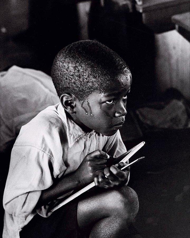 Studente lotta per seguire la lezione scolastica (Sud Africa, 1966). Fotografia di Ernest Cole