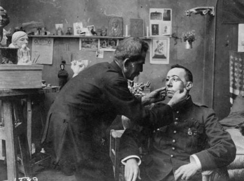 Un soldato francese, il cui volto è stato mutilato durante la prima guerra mondiale, viene dotato di una maschera realizzata dalla Croce Rossa, 1918