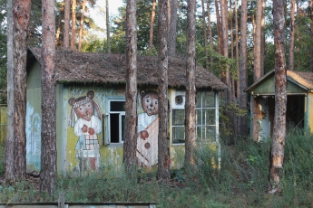 Izumrudniy' ('Emerald') Holiday Camp, near Chornobyl. Once a popular spot for summer holiday breaks, these rustic wooden chalets, painted with characters from cartoons and fairy tales, were completely destroyed by forest fires in April 2020. Chernobyl Exclusion Zone by Darmon Richter