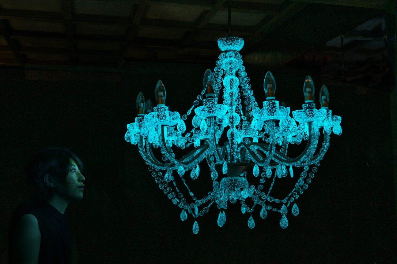 "Rui Sasaki. ""Weather Chandelier"" (2015), glass, phosphorescent crystal mixture, metal, timer, motion detector, solar panel, sunshine, 700 x 550 millimeters. Photo by Kichiro Okamura, collection of Glasmuseet Ebeltoft"