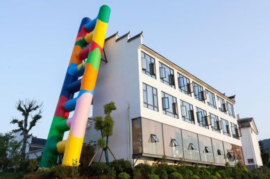 Italian artist Paola Pivi ascends at FULIANG 2021 with a monumental installation entitled Untitled (ladder). The installation consists of a graphic inflatable staircase over 20 meters tall propped against a banal two-story building.