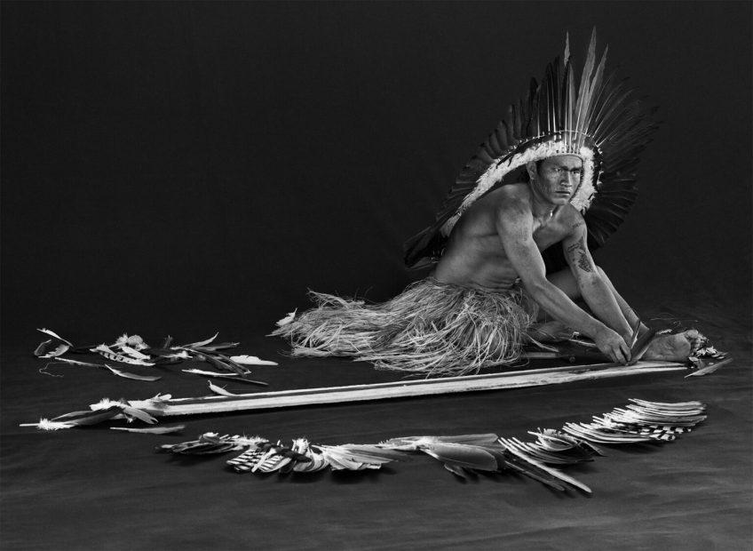 Miró (Viná) Yawanawá che realizza ornamenti di piume, una delle arti che un principiante deve imparare a padroneggiare. Territorio indigeno di Rio Gregório, stato di Acri, 2016. Fotografia di Sebastião Salgado